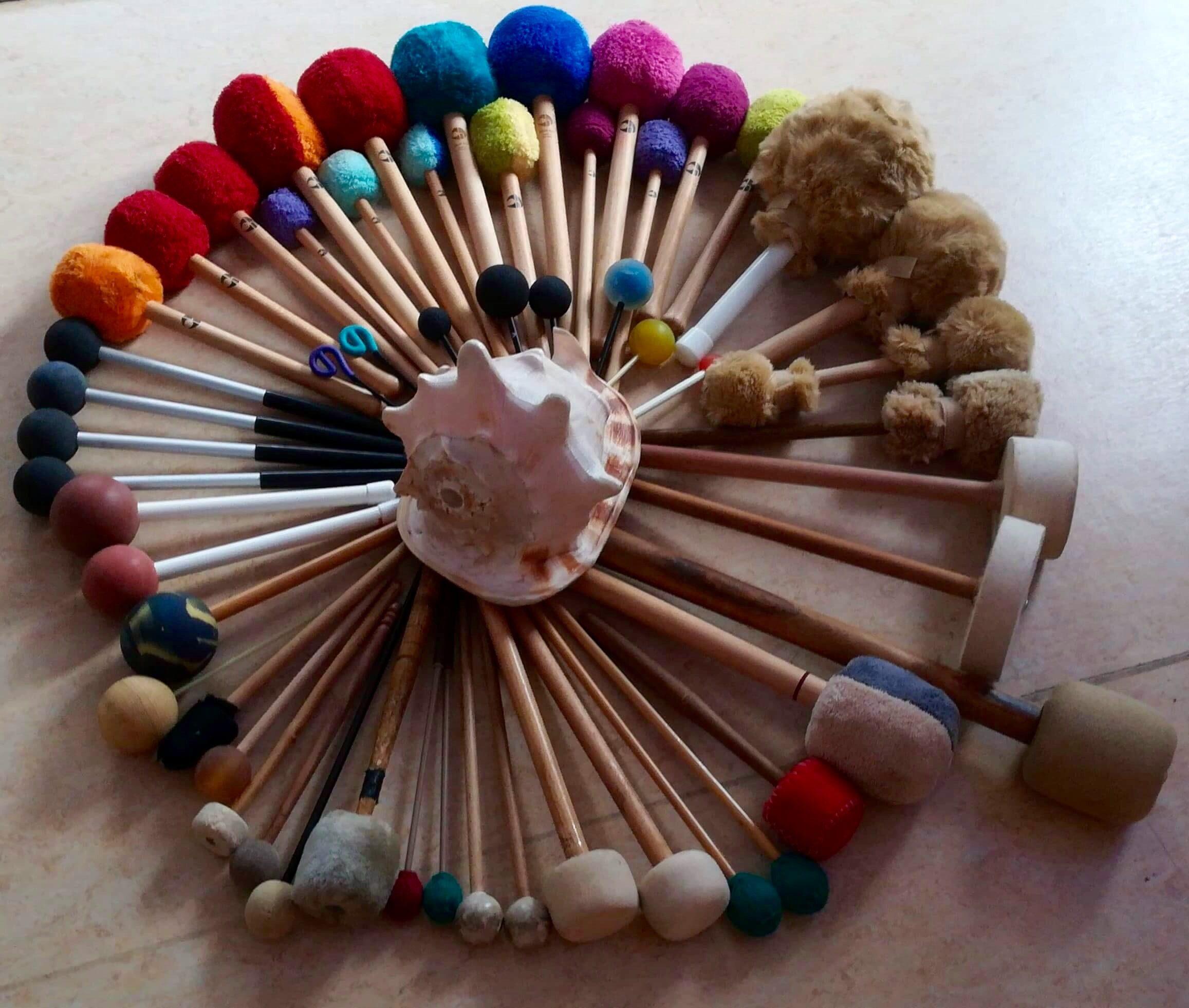 47 Gongklöppel im Kreis angeordnet, auf dem Mittelpunkt liegt eine Muschel