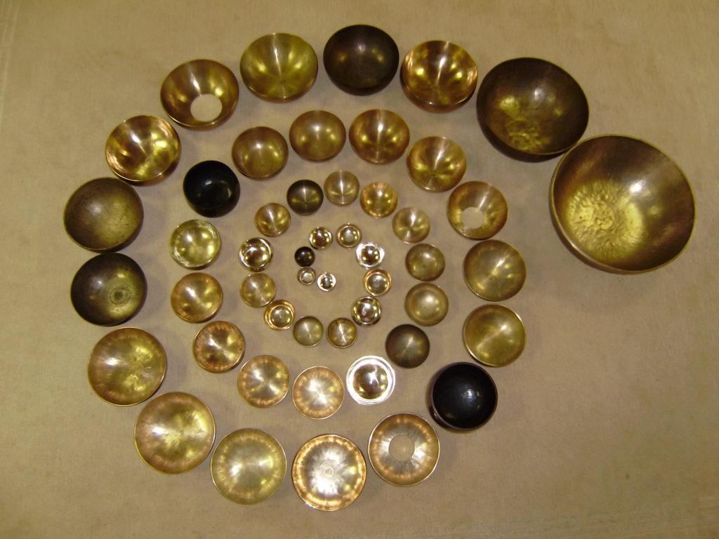 50 Klangschalen nach größe sortiert linksläufig in einer Spirale angeordnet