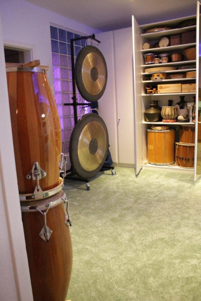 Aufgestapelte Congas, zwei Gongs am Ständer und verstaute Perkussionsinstrumente